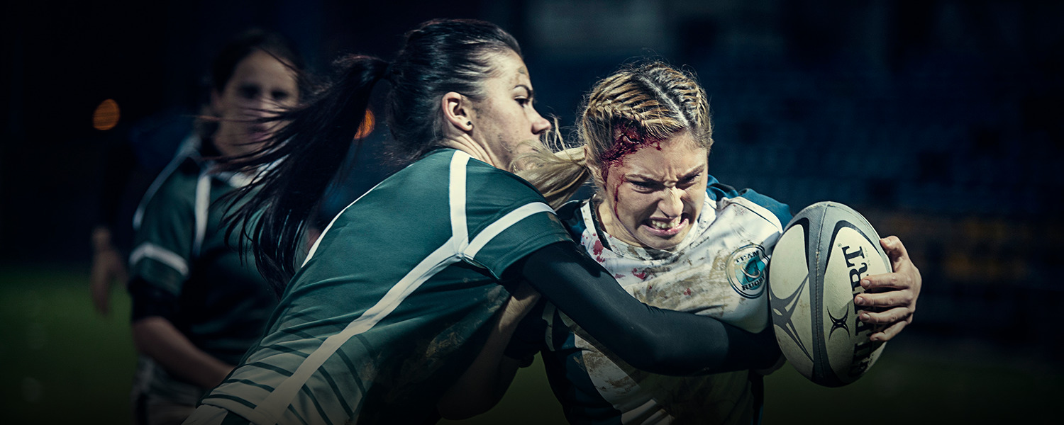 Female rugby player with an injury being tackled by her opponents - Libresse